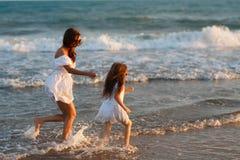 母亲和小女儿获得在海滩的乐趣 免版税库存照片