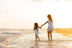 母亲和小女儿获得在海滩的乐趣 库存图片