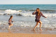 母亲和小女儿获得在海滩的乐趣 图库摄影
