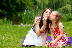 母亲和小女孩吹的肥皂泡在公园 免版税库存图片