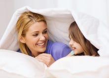 母亲和小女孩在毯子下在家 库存图片