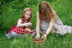 母亲和小女孩有樱桃篮子的  免版税库存图片
