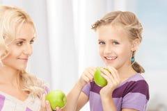 母亲和小女孩用绿色苹果 免版税库存照片