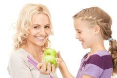 母亲和小女孩用绿色苹果 免版税库存图片