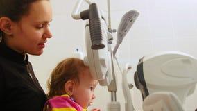 母亲和小女孩-验光师检查儿童` s眼睛-儿童眼科学 股票视频