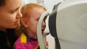 母亲和小女孩-验光师检查儿童` s眼睛-儿童眼科学 股票录像