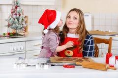 母亲和小孩女孩烘烤圣诞节的姜饼曲奇饼 免版税库存照片