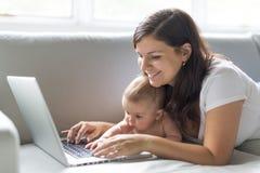 母亲和小孩子在长沙发看在家演奏和读计算机 免版税库存照片