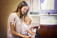 母亲和小孩男婴,在家弹钢琴 库存照片
