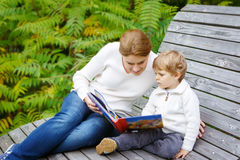 年轻母亲和小孩男孩阅读书在秋天停放 免版税库存照片