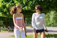母亲和少年的通信 妇女与13年的青少年的女儿谈话 都市背景的样式 免版税库存照片