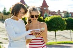 母亲和少年的通信 妇女与13年的青少年的女儿谈话 都市背景的样式 库存照片