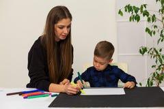 母亲和年轻儿子画图片在桌上 免版税库存照片