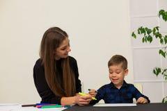 母亲和年轻儿子画图片在桌上 免版税库存图片
