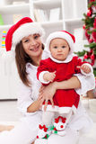 母亲和庆祝圣诞节的女婴 免版税库存图片