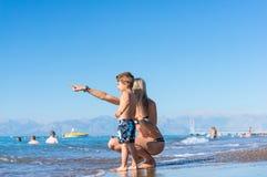 年轻母亲和微笑使用在天时间的海滩的男婴儿子 正面人的情感,感觉, 库存照片