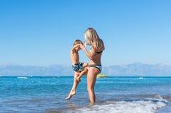 年轻母亲和微笑使用在天时间的海滩的男婴儿子 库存图片