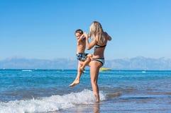 年轻母亲和微笑使用在海滩的男婴儿子天时间 库存图片