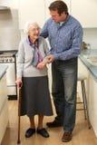 母亲和成人儿子在厨房里 免版税库存图片