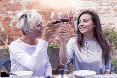 母亲和成人女儿品尝酒坐室外 免版税库存照片