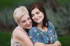 母亲和成人女儿在一起摆在一个绿色的公园 免版税库存照片
