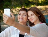母亲和成人女儿由手机做着selfie在su 免版税库存照片