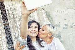 母亲和成人女儿采取selfie户外 库存照片