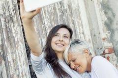 母亲和成人女儿采取selfie户外 免版税库存图片