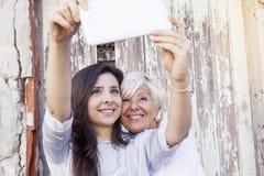 母亲和成人女儿采取selfie 库存照片