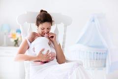 年轻母亲和新出生的婴孩在白色卧室 图库摄影