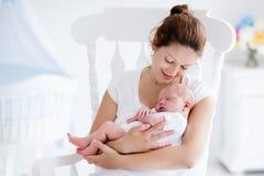 年轻母亲和新出生的婴孩在白色卧室 免版税库存照片