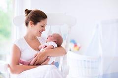 母亲和新出生的婴孩在白色托儿所 免版税库存图片