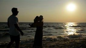 母亲和父亲三个黑暗的剪影有小女儿的在海附近在日落期间 股票录像