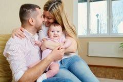 母亲和父亲有一个婴孩的在拥抱微笑的屋子里愉快 库存图片
