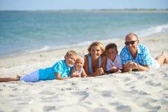 母亲和父亲有三个孩子的海滩的 库存图片