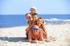 母亲和父亲有三个孩子的海滩的 免版税库存照片