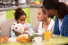 母亲和父亲有小孩和狗的在桌上 免版税库存照片