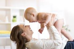 母亲和男婴使用在晴朗的屋子里的尿布的 的父母和在家放松的小孩 一起有系列的乐趣 免版税库存图片
