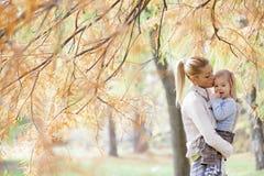 母亲和男孩在秋天森林里 免版税库存照片