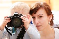 母亲和男孩孩子哄骗有拍照片的照相机的儿子。在家。 免版税库存照片