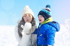 母亲和男婴在白色多雪的天,冬天假期 免版税图库摄影