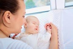 母亲和睡觉的孩子在窗口附近 系列愉快爱 库存照片