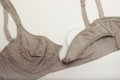 母亲和硅乳头的护理胸罩 与新的一次性乳房垫的妈妈胸罩 防止流程在衣裳的牛奶,它 库存图片