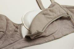 母亲和硅乳头的护理胸罩 与新的一次性乳房垫的妈妈胸罩 防止流程在衣裳的牛奶,它 免版税图库摄影