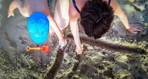 母亲和获得的孩子在海滩的乐趣 r 库存照片