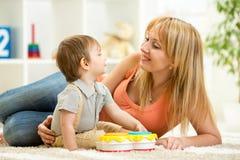 母亲和获得的男婴与音乐玩具的乐趣 图库摄影