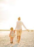 母亲和走在海滩的女婴 免版税库存图片