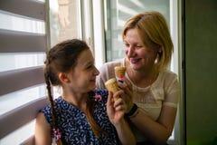母亲和逗人喜爱的女儿在一个热的夏日享用冰淇淋 库存图片