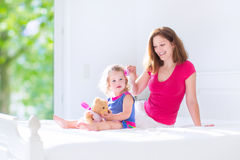 母亲和逗人喜爱的女儿掠过的头发 免版税库存照片