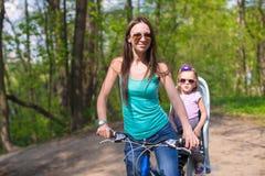 年轻母亲和逗人喜爱的小的女儿骑马一起骑自行车 免版税库存照片